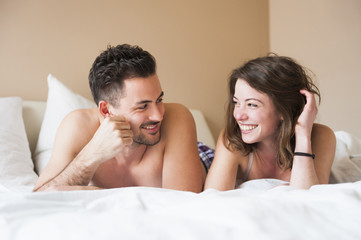 Young couple lying in bed gazing at each other