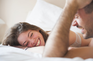 Over shoulder view of young couple lying in bed