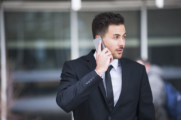 Young businessman outside office talking on smartphone
