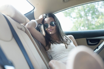 Young woman sitting, relaxing, in back seat of car