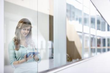 Businesswoman using digital tablet behind office window