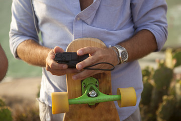 Man holding camera and skateboard
