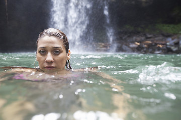 Woman swimming, waterfall in background