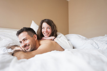 Young woman lying on top of boyfriend in bed