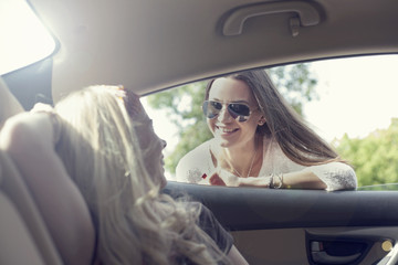 Young woman, taking to friend through car window