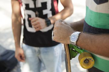 Cropped shot of father and son skateboarders on sidewalk, Copacabana, Rio De Janeiro, Brazil