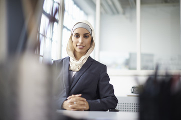 Portrait of young businesswoman wearing hijab at office desk