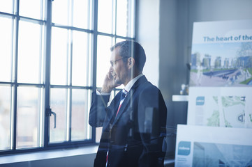 Business man chatting on smartphone whilst looking out of office window