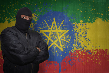 dangerous man in a mask standing near a wall with painted national flag of ethiopia