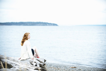 Young woman sitting on beach looking out to sea, Bainbridge Island, Washington State, USA