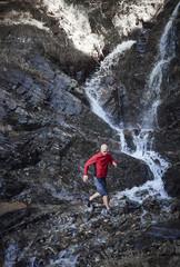 Mature man trail running by waterfall, Valais, Switzerland