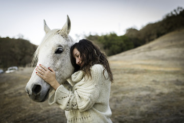Young woman leaning against and petting white horse in field