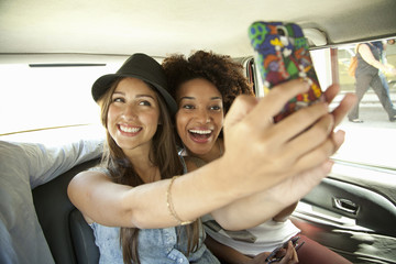 Young women taking photo of themselves in car