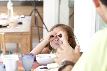 Father and daughter sitting at breakfast table, daughter making binoculars from fingers