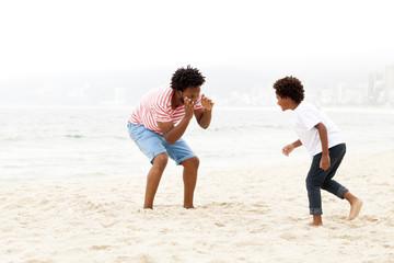 Father and son playing on beach, RIo de Janeiro, Brazil