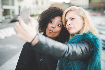 Two young women pulling faces for smartphone selfie, Lake Como, Como, Italy