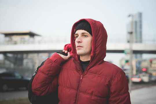 Young man wearing red hooded anorak on city street