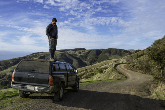 Man looking down from top of pick up truck, Big Sur, California, USA
