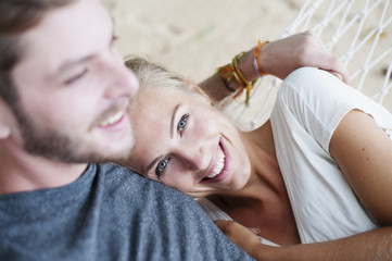 Close up of smiling young couple on beach hammock