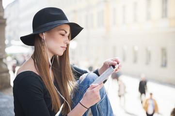 Stylish young woman choosing smartphone music on city step
