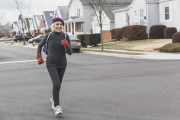 Senior woman jogging in street