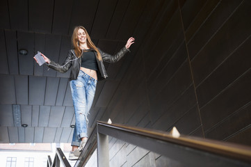 Young woman balancing on city stairway banister