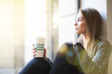 Portrait of beautiful young woman gazing out of cafe window