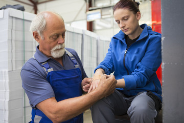 Factory worker applying first aid to colleague