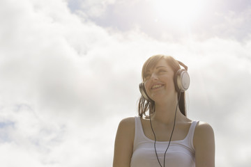 Young woman wearing headphones under bright sunny sky