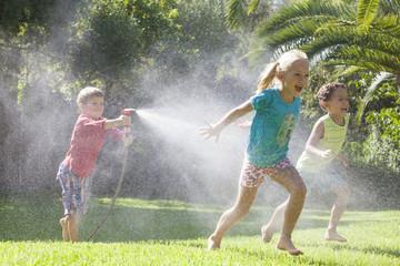 Three children in garden chasing each other with water sprinkler