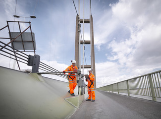 Bridge workers inspecting suspension bridge cables. The Humber Bridge, UK was built in 1981 and at the time was the world's largest single-span suspension bridge