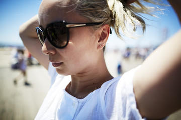 Portrait of woman wearing sunglasses putting hair up