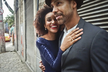 Couple standing together in urban environment, hugging, smiling