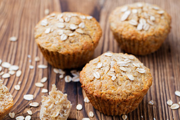 Healthy vegan oat muffins, apple and banana cakes on a wooden background.