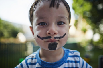 Close up portrait of boy looking at camera wearing beard and moustache face paint costume