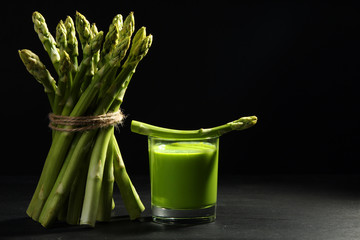 fresh asparagus tied rope and fresh juice of asparagus in a glass on a back wooden background