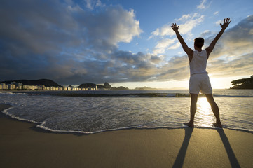 Athlete standing with arms raised against a scenic sunrise view of Sugarloaf Mountain at Copacabana Beach in Rio de Janeiro, Brazil