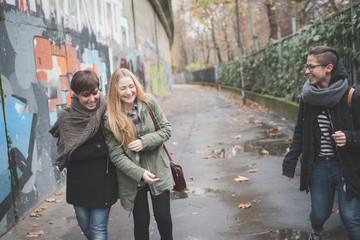 Three sisters walking by graffiti wall