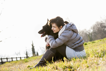 Mid adult woman and her dog sitting on hillside