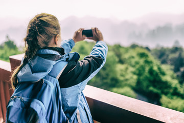 Young female tourist taking photo of mountains. Toned image