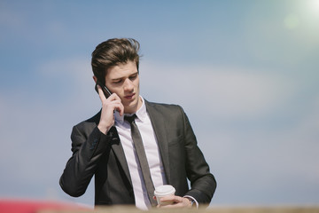 Young businessman chatting on smartphone whilst drinking takeaway coffee