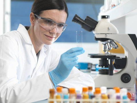Scientist holding microscope slide with blood sample in lab