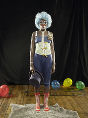 Portrait of young woman wearing clown face paint and blue wig on stage