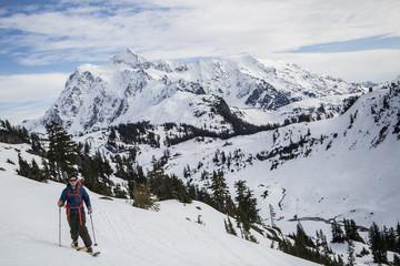 Young male skier moving along mountainside, Mount Baker, Washington, USA
