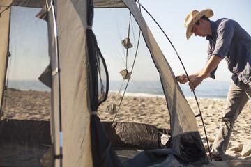 Man setting up tent on beach, Malibu, California, USA