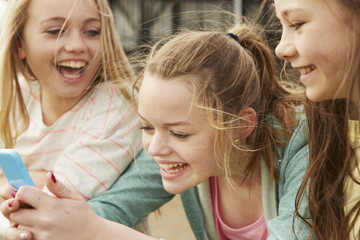 Three girls laughing at smartphone text