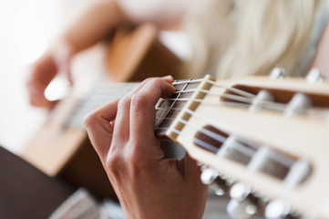 Hands of young woman playing acoustic guitar