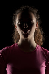 portrait of a girl with the face in shadow on a dark background