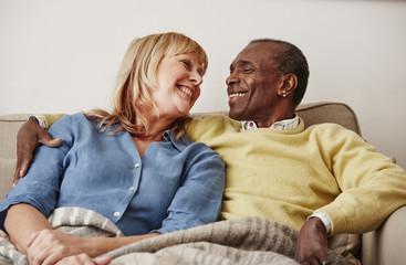 Couple sitting on sofa, smiling