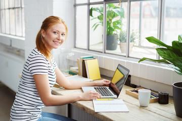 moderne junge frau sitzt zuhause am schreibtisch und arbeitet am laptop